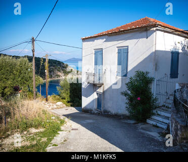 White painted villa with blue shutters in the small fishing village of Kioni in the Greek Ionian Islands - Stock Photo