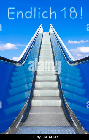 Escalator into a blue sky, concept of achievement, ENDLICH 18 german text, meaning FINALLY 18, adulthood and freedom - Stock Photo