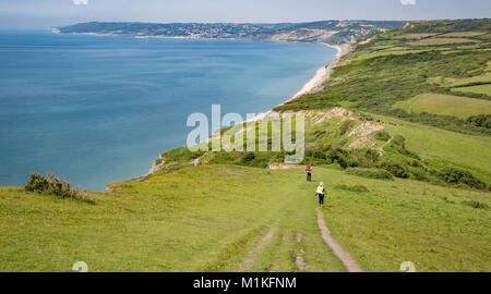 Walkers descending from Golden Cap the highest point on the southern section of the South West coast path towards - Stock Photo