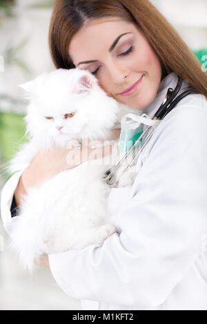 young female vet hugging white Persian cat - Stock Photo