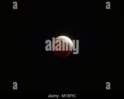 Super blue blood moon with partial lunar eclipse over dark sky background - Stock Photo