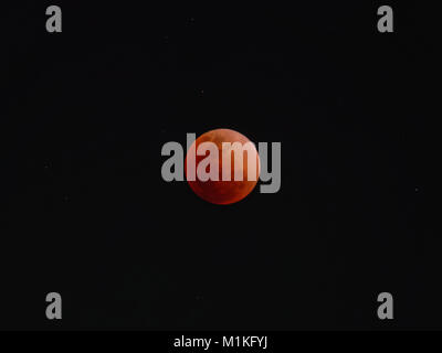 Super blue blood moon with total lunar eclipse over dark sky background - Stock Photo