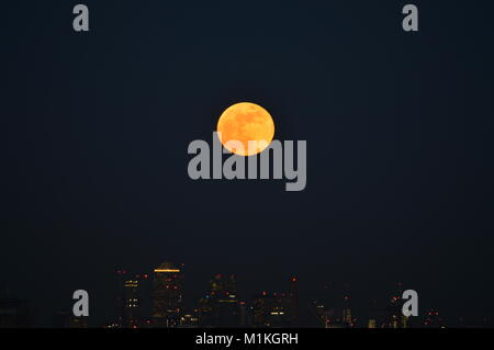 A super blue blood moon rising over Canary Wharf, London, UK - Stock Photo