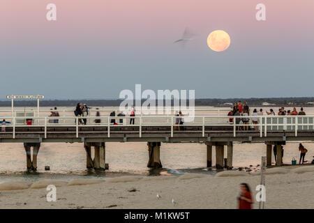 Busselton, Western Australia. 31st Janauary 2018. People watching the Super moon rising above Busselton Jetty.  - Stock Photo