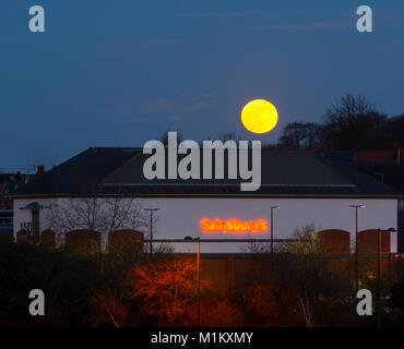 Warwick, UK. 31st January, 2018. The 'super blue' moon rises over Sainsbury`s supermarket store in Warwick, UK. - Stock Photo