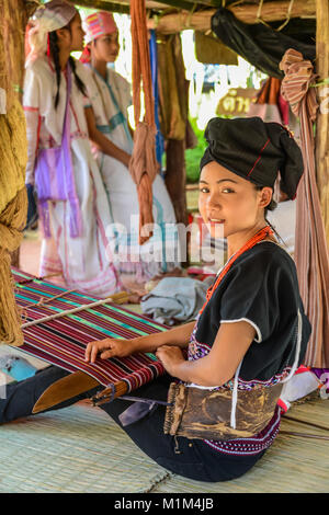 CHIANGMAI, THAILAND - JANUARY 24, 2015: Hill tribe girl  demonstrating weaving fabric in 22nd Traditional Skirt - Stock Photo