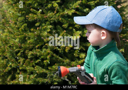 A child, a boy, watering a rubber hose in a garden, a country house, watering - Stock Photo