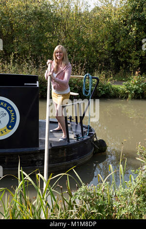 Woman using a wooden pole to cast off a narrowboat off from the shore - Stock Photo