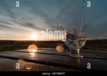 Water splash in the sunset frozen in motion. Teal and orange look against the sunlight with lensflares - Stock Photo