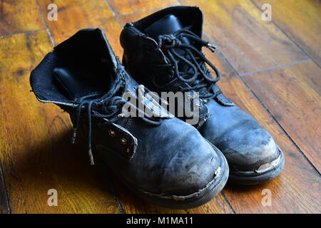 worn out leather work boots - Stock Photo