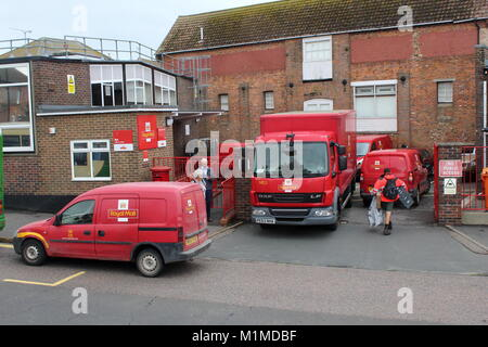 A BUSY SCENE WITH RED ROYAL MAIL DELIVERY VANS AND TRUCK OUTSIDE A TOWN CENTRE DELIVERY OFFICE IN RYE,EAST SUSSEX