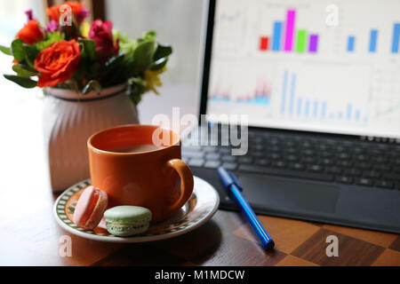 Cup of coffee with milk on the table on a foreground next to the working computer and vase with beautiful flowers - Stock Photo