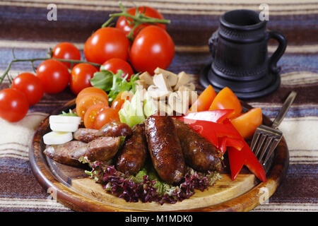 fried sausage, salad, tomatoes, mushrooms, sweet peppers on a wooden stand - Stock Photo