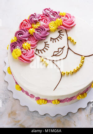 Festive cake with cream flowers and a girl face on a light background - Stock Photo