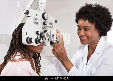 Female African Optometrist Doing Sight Testing For Patient In Hospital - Stock Photo