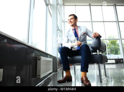 Low angle shot of a handsome young businessman in a stylish modern office space with large windows.
