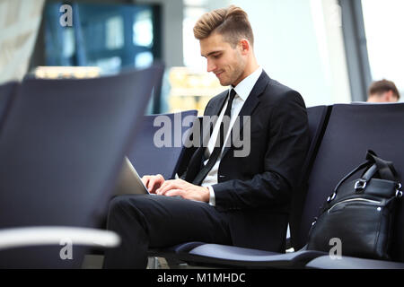 Young adult using laptop in airport lounge - Stock Photo