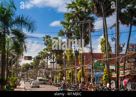 A typical road in Kata with a lot of motorbikes parking at the roadside under a row of palm trees and utility poles. - Stock Photo