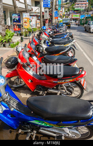 A typical scene in southeast Asia. A lot of motorbikes parking very close to each other in a row at the roadside - Stock Photo