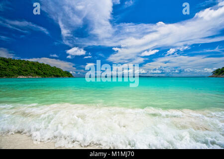 Turquoise waves rushing to the beautiful shore of Siam Bay, flanked by hills, on Ko Racha Yai. - Stock Photo