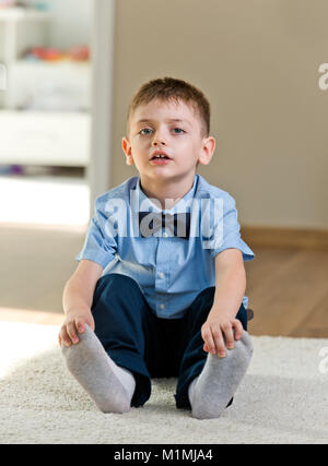 Six years old boy preparing for his first day of school, in blue shirt, at home. - Stock Photo