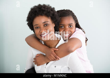 Portrait Of A Daughter Embracing Her Mother From Behind Against White Background - Stock Photo