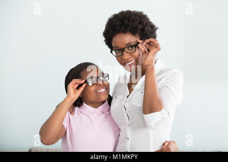 Portrait Of A Smiling Daughter And Mother With Eyeglasses Against White Background - Stock Photo
