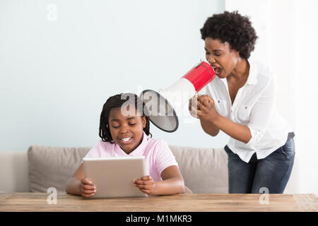 Mother Shouting At Her Daughter Holding Digital Tablet In A Megaphone At Home - Stock Photo