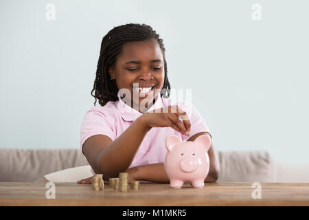 Portrait Of An African Girl Inserting Coins In Pink Piggy Bank On Table - Stock Photo