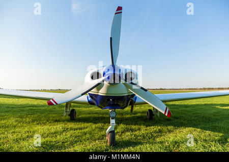 The propeller of a white airplane on the grass close up. Airplane propeller. - Stock Photo