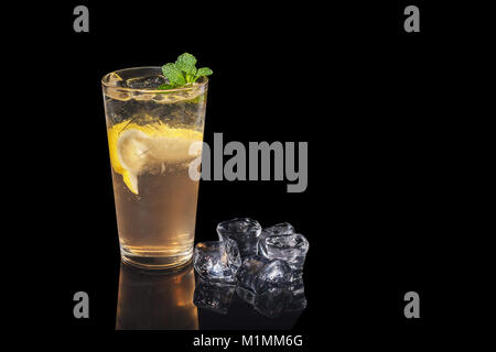 alcohol cocktail with lemon and mint on a black background - Stock Photo