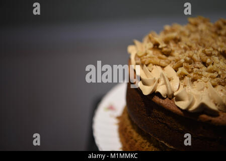 delicious homemade coffee cake with buttercream top and sprinkled with nuts and a dark background - Stock Photo