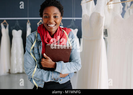 Cheerful bridal store owner standing in her boutique with a diary. Female wedding fashion designer in a bridal boutique. - Stock Photo