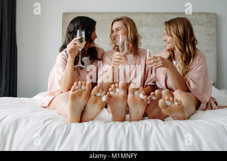 Happy bridesmaids and bride in silk robes sitting on bed and smiling. Celebrating hen party at home. - Stock Photo