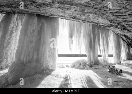 A sun burst shines around an ice column curtain on Grand Island near Munising Michigan in winter