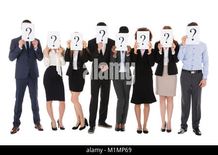 Businesspeople Hiding Behind Question Mark Sign Against White Background - Stock Photo