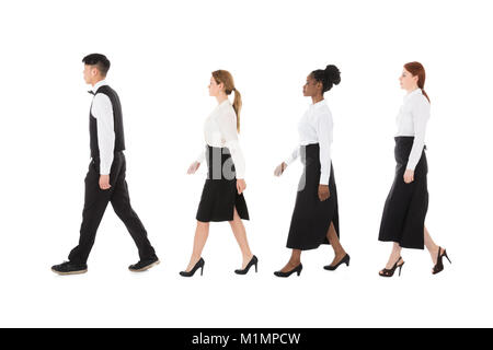 Young Restaurant Staff Walking In Row Against White Background - Stock Photo