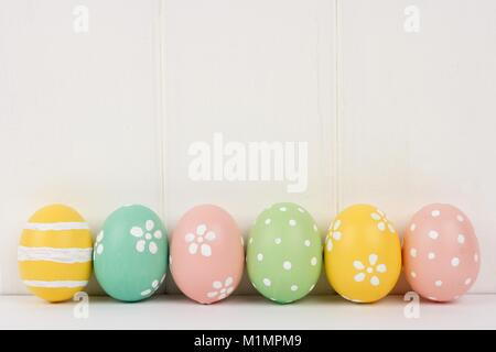Row of hand painted Easter eggs over a white wooden background - Stock Photo