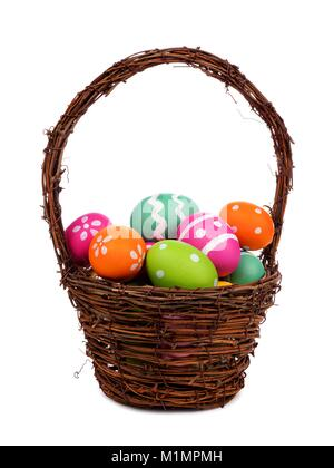Easter basket filled with colorful hand painted Easter Eggs over a white background - Stock Photo