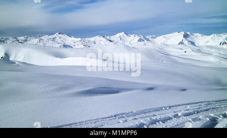 Fresh snow on ski pistes, covering valleys and peaks, with rugged mountain tops panorama, on a clear winter day, - Stock Photo