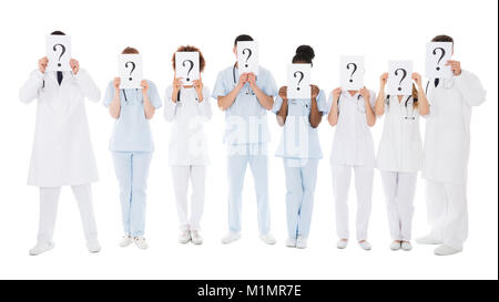 Group Of Multiracial Doctors Hiding Behind Question Mark Sign Over White Background - Stock Photo