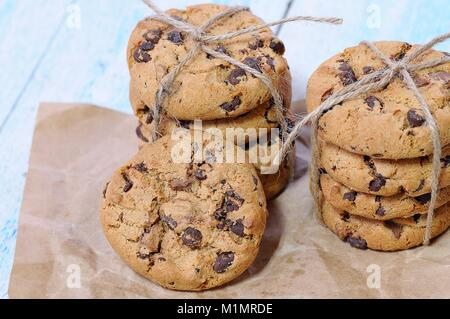 Stacks of homemade chocolate chip cookies on wooden table - Stock Photo
