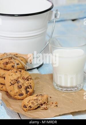 One bitten and stack of chocolate chip cookies with glass of milk on baking paper. Bucket on background. - Stock Photo