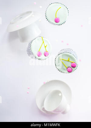 White tea set with a spoon and levitating colorful cup-cakes and sugar stars - Stock Photo