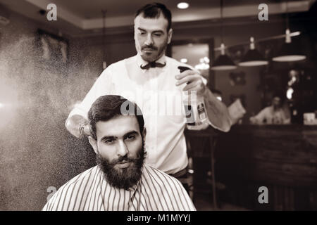 The barber sprinkles on the hair of a young male client of a barber shop with water from a bulb. - Stock Photo