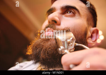 a young manly man with a beard in barbershop - Stock Photo