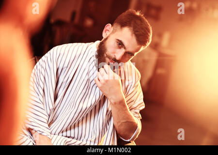 a handsome brave man with a beard in a barbershop - Stock Photo