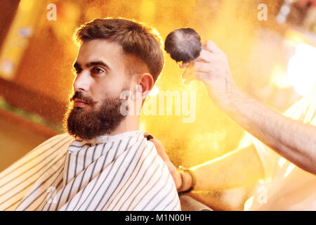 barber does a haircut for a young handsome man with a beard and mustache  - Stock Photo