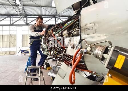 Aircraft mechanic repairs an aircraft engine in an airport hangar - Stock Photo