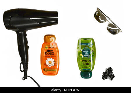 22 January 2018-Bucharest, Romania. Two bottles of Garnier shampoo along with a hair dryer, hair clip and sunglasses. - Stock Photo